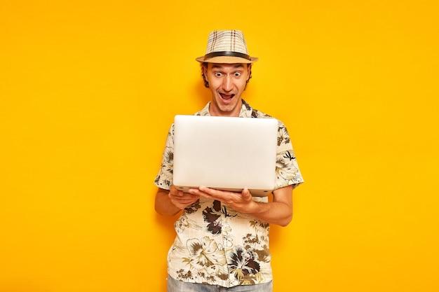 Verrast mannelijke toerist met laptop in zijn handen is geïsoleerd op gele achtergrond met ruimte voor tekst