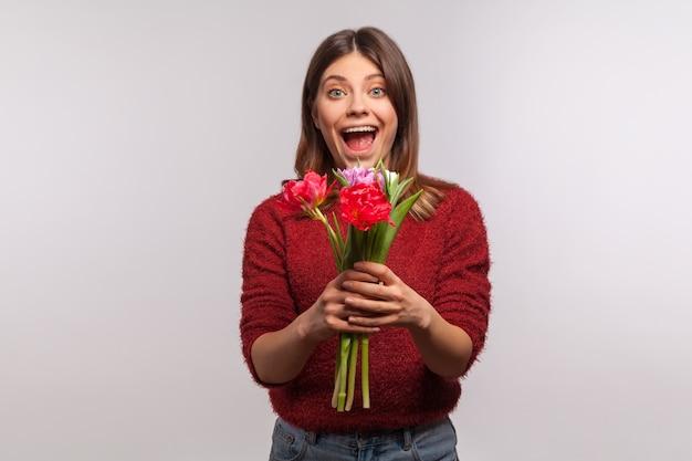 Verrast meisje dat bloemtulp vasthoudt en naar de camera kijkt met een verbaasd gezicht