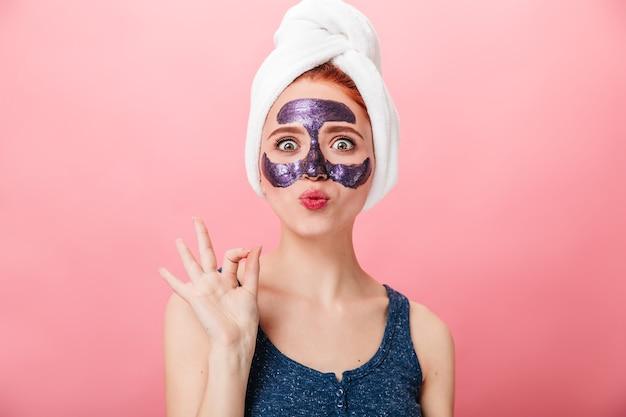 Verrast meisje dat goed teken toont tijdens huidverzorgingsbehandeling. vooraanzicht van verbaasde vrouw met gezichtsmasker geïsoleerd op roze achtergrond.