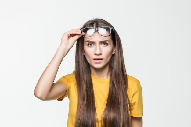 Verrast meisje dat haar die glazen opstijgt op witte muur wordt geïsoleerd