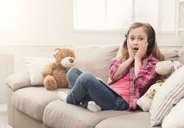Verrast meisje dat online games speelt op tablet en naar muziek luistert in een koptelefoon. vrouwelijke kind zittend op de bank met haar teddybeer. schokkend inhoud en sociaal netwerkconcept
