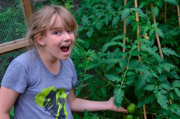 Verrast meisje die tomaten, meer van het hout, ontario, canada tonen