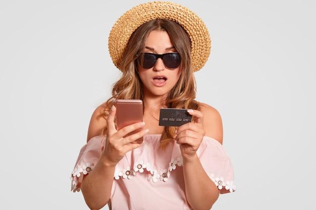 Verrast meisje gekleed in modieuze blouse, strooien hoed en tinten, maakt gebruik van mobiele telefoon en creditcard
