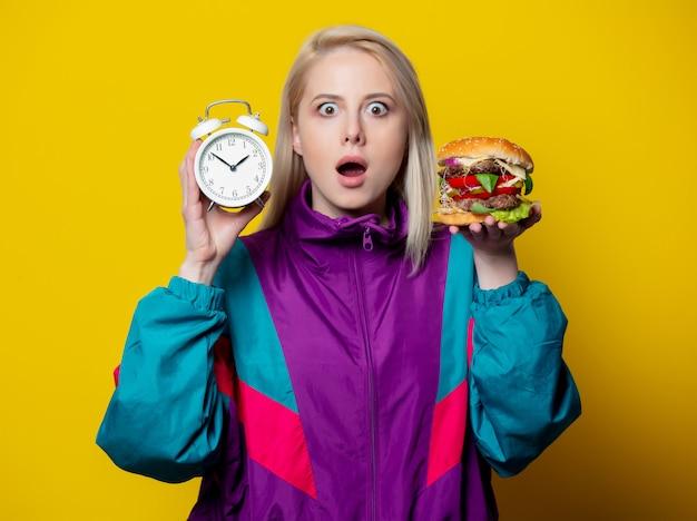 Verrast meisje in 80s kledingstijl met hamburger en wekker