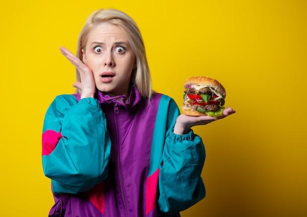 Verrast meisje in 80s kledingstijl met hamburger op gele ruimte