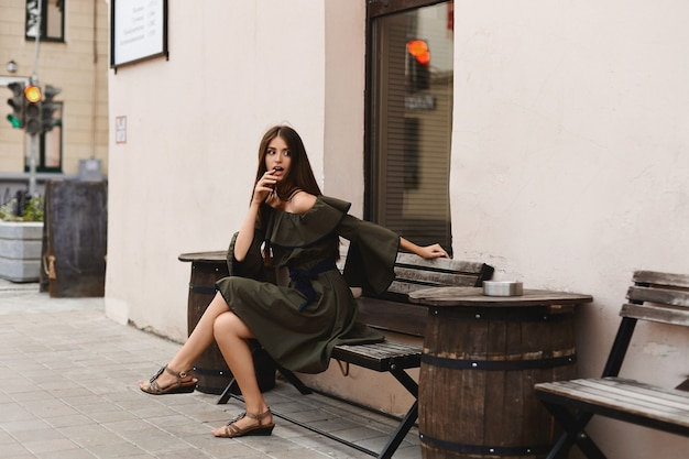 Verrast meisje in een lichte kledingszitting op de bank en kijkend opzij.