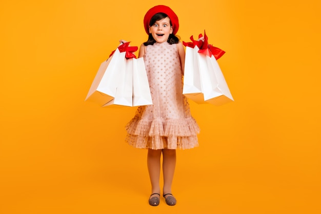 Verrast meisje in franse baret poseren na het winkelen. verbaasd kind met papieren zakken.