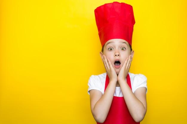 Verrast meisje in het pak van een rode chef-kok met handen op de wangen, mond wijd open