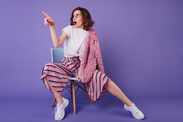 Verrast meisje in trendy broek zittend op een stoel en wegkijken. indoor portret van stijlvolle brunette dame in witte sneakers verbazing uiten tijdens fotoshoot op paarse muur.