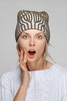 Verrast meisje in witte trui en gebreide muts met wijd open mond