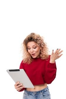 Verrast meisje leest berichten op tablet op wit