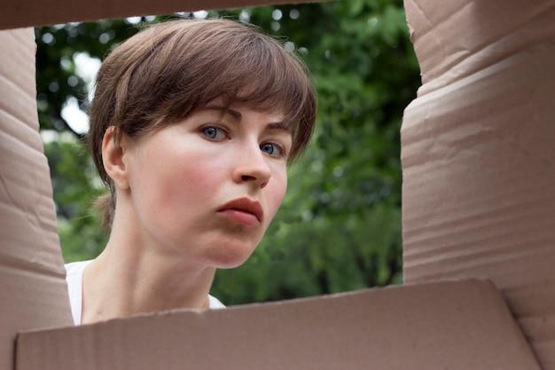 Verrast meisje met blauwe ogen, uitzicht vanaf kartonnen doos