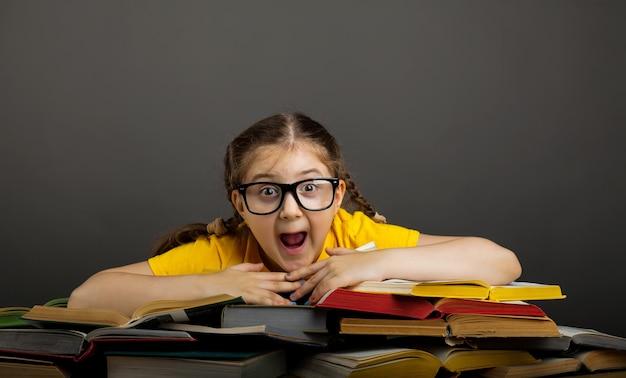 Verrast meisje met boeken dichtbij schoolbord. lege ruimte voor tekst