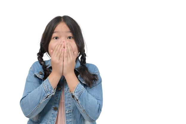 Verrast meisje met een spijkerjasje dat haar mond bedekt en naar camera kijkt die op een witte achtergrond is geïsoleerd, geschokt emotieconcept