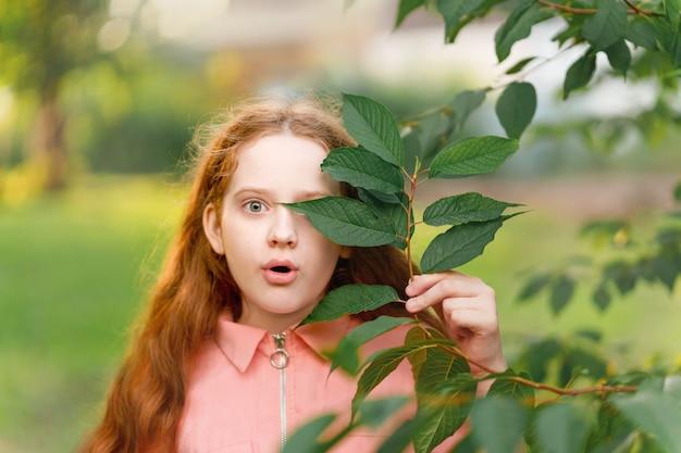 Verrast meisje met een tak met groene bladeren in de buurt van haar gezicht