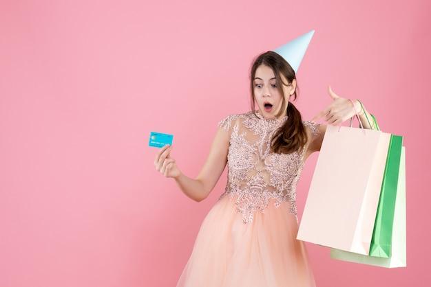 Verrast meisje met feestmuts met creditcard en boodschappentassen op roze