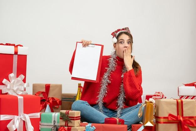 Verrast meisje met kerstmuts bedrijf documenten zitten presenteert op wit