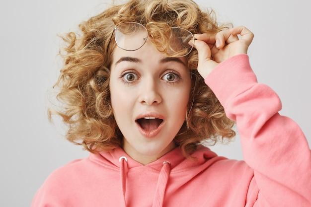 Verrast meisje met krullend haar neemt een bril af en zegt wow verbaasd