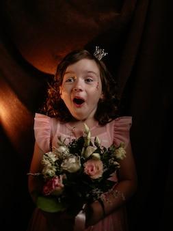 Verrast meisje met make-up en kapsel houdt een boeket bloemen op een bruine achtergrond