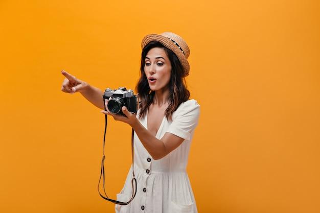 Verrast meisje met retro camera toont vinger in de verte. schattige brunette met kort haar in lichte stijlvolle kleding poseren.