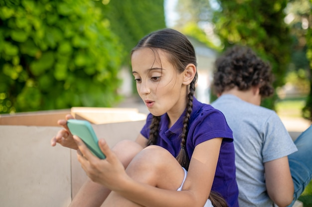 Verrast meisje met smartphone en jongen terug