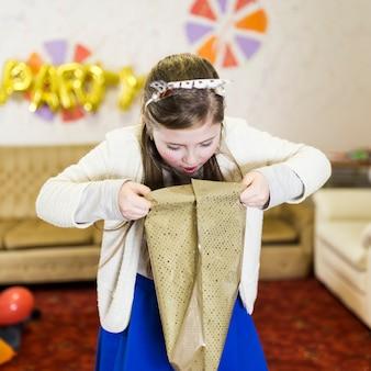 Verrast meisje uitpakken verjaardagscadeau