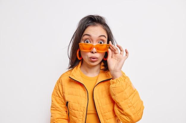 Verrast modieuze brunette jonge aziatische vrouw draagt trendy oranje zonnebril jas en oorbellen reageert op iets verbazingwekkends geïsoleerd over witte muur. stijl en mode concept.