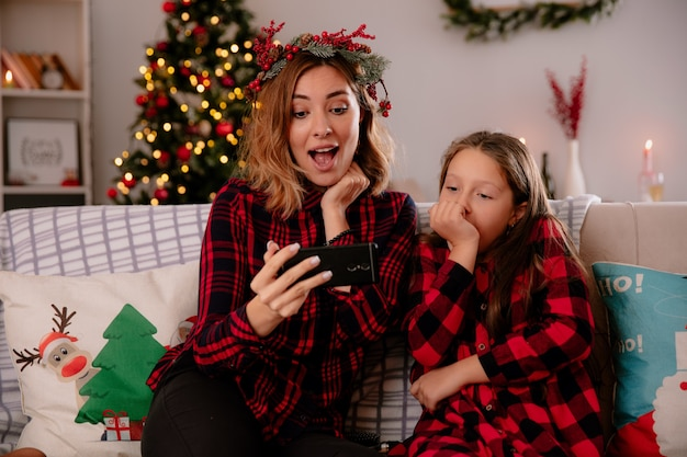Verrast moeder en dochter kijken naar telefoon zittend op de bank en genieten van kersttijd thuis