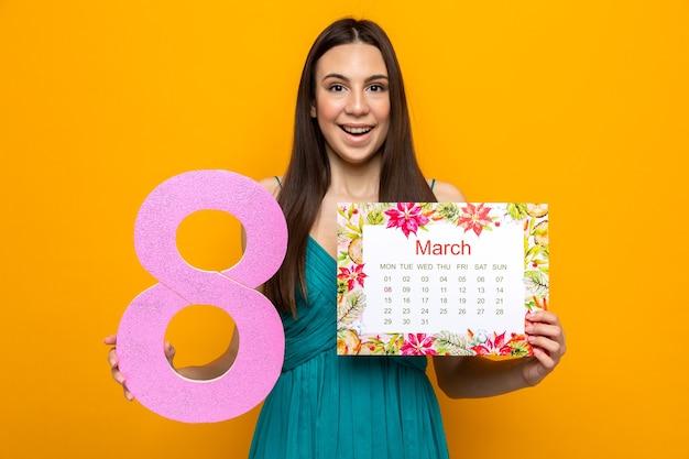 Verrast mooi jong meisje op gelukkige vrouwendag met kalender met nummer acht geïsoleerd op oranje muur