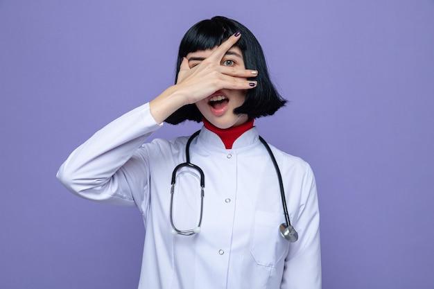 Verrast, mooi kaukasisch meisje in doktersuniform met een stethoscoop die haar gezicht bedekt met de hand en naar de voorkant kijkt door de vingers