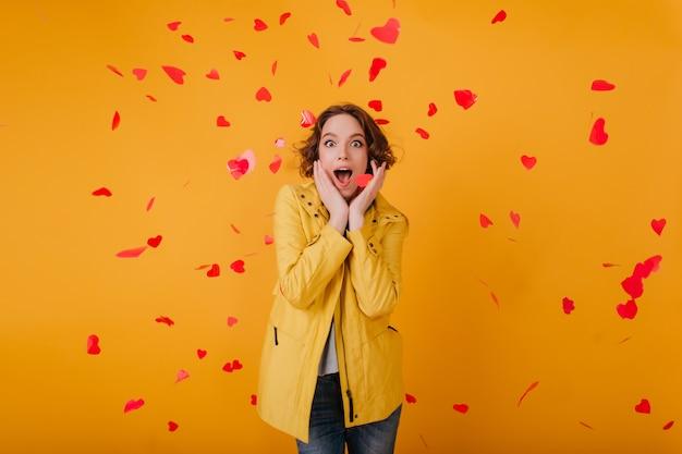 Verrast mooi meisje in vrijetijdskleding met plezier in valentijnsdag. indoor foto van spectaculaire vrouw omringd door rode harten.