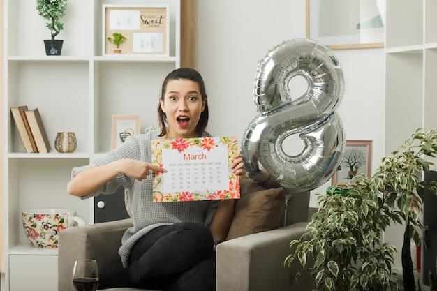 Verrast mooi meisje op gelukkige vrouwendag en wijst naar kalender zittend op een fauteuil in de woonkamer