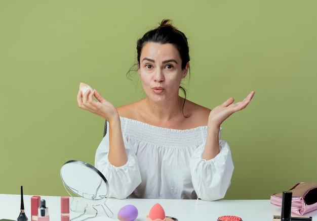 Verrast mooi meisje zit aan tafel met make-up tools foundation met spons op zoek geïsoleerd op groene muur toe te passen