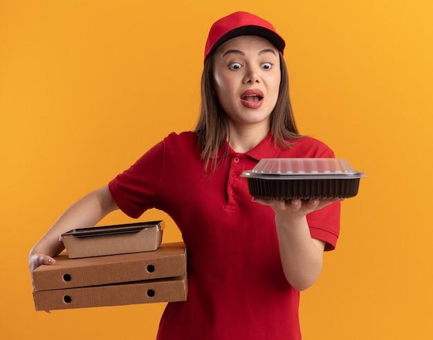 Verrast mooie bezorger in uniform houdt papieren voedselpakket op pizzadozen en kijkt naar voedselcontainer geïsoleerd op oranje muur met kopieerruimte