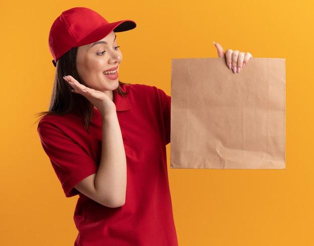 Verrast mooie bezorger in uniform staat met opgeheven hand en kijkt naar een papieren pakket geïsoleerd op een oranje muur met kopieerruimte