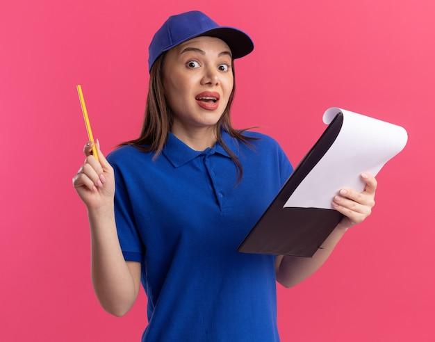 Verrast mooie bezorgvrouw in uniform met potlood en klembord op roze