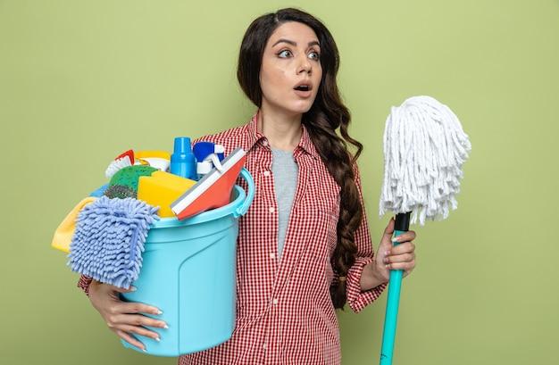 Verrast, mooie blanke schonere vrouw die schoonmaakapparatuur en menigte vasthoudt en naar de zijkant kijkt