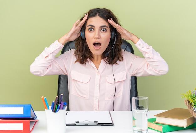 Verrast mooie blanke vrouwelijke callcenter-operator op koptelefoon zittend aan bureau met kantoorgereedschap handen op haar hoofd zetten