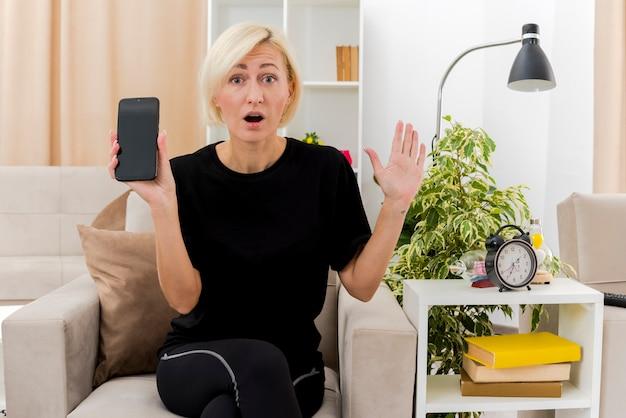 Verrast mooie blonde russische vrouw zit op fauteuil hand opheffen en telefoon in de woonkamer te houden