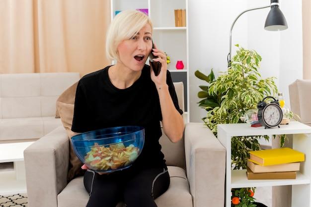 Verrast mooie blonde russische vrouw zit op fauteuil praten over de telefoon met kom chips in de woonkamer