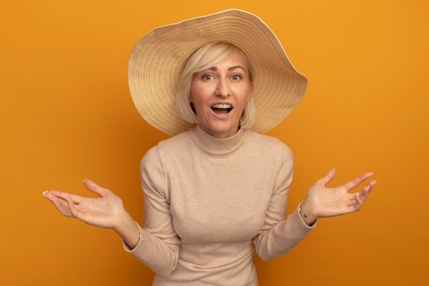 Verrast mooie blonde slavische vrouw met strandhoed houdt handen open en kijkt naar de camera op oranje