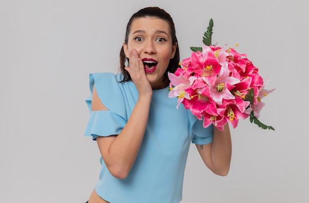 Verrast mooie jonge vrouw die een boeket bloemen vasthoudt en hand op haar gezicht legt