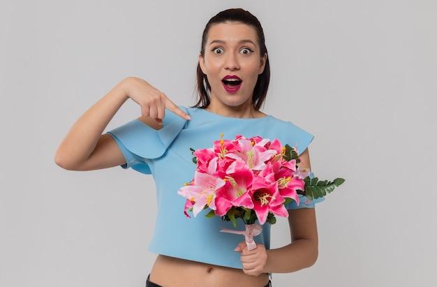 Verrast mooie jonge vrouw houden en wijzend op boeket bloemen