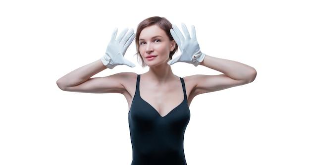 Verrast mooie jonge vrouw in witte handschoenen poseren in de studio op een wit