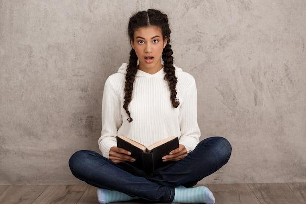 Verrast mooie jonge vrouw met boek, zittend op beige muur