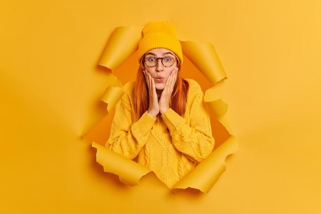 Verrast mooie roodharige vrouw houdt handen op wangen ziet iets ongelooflijks staart draagt gele trui en hoed breekt door papieren gat. verbaasd onder de indruk vrouw binnenshuis
