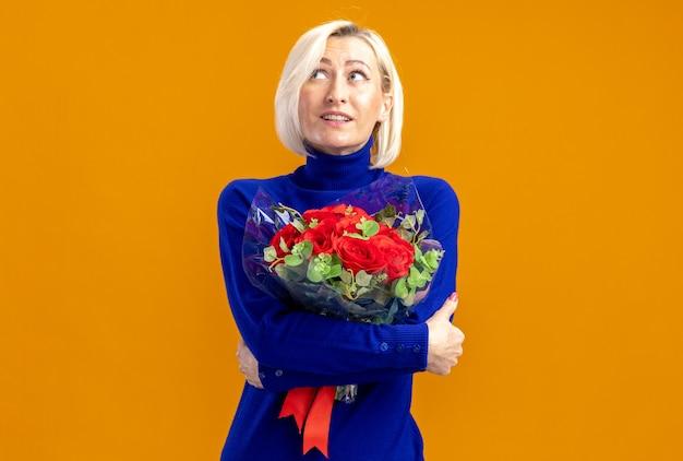Verrast mooie slavische vrouw die een boeket bloemen vasthoudt en op valentijnsdag naar de zijkant kijkt