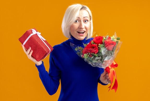 Verrast mooie slavische vrouw met boeket bloemen en geschenkdoos op valentijnsdag