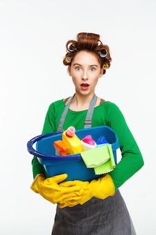 Verrast mooie vrouw houdt blauwe emmer vol met schoonmaak tools