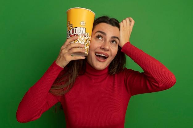 Verrast mooie vrouw houdt emmer popcorn dicht bij het hoofd en legt de hand op het hoofd geïsoleerd op groene muur